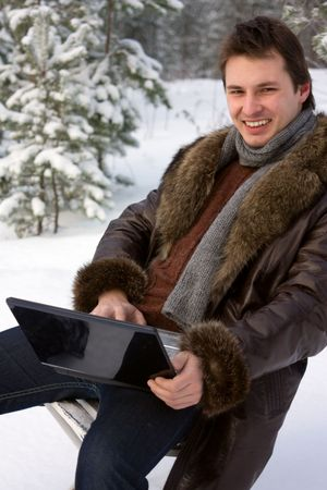 young smiling man with laptop outdoors