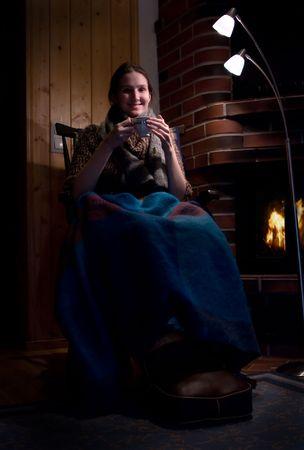 young woman drinking tea near fireplace