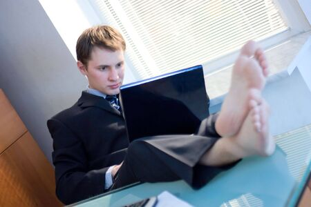 young businessman working in office barefooted photo