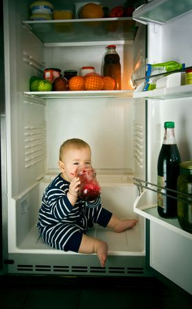 little boy eating jam in fridge Standard-Bild