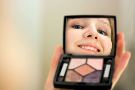 appreciating: young woman looking at oneself in mirror Stock Photo