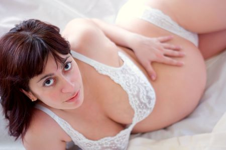 young beautiful pregnant woman lying on bed photo