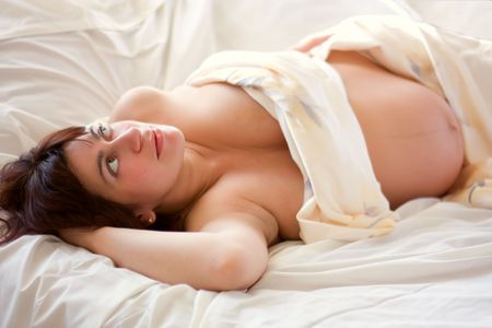 young beautiful pregnant woman lying on bed Stock Photo