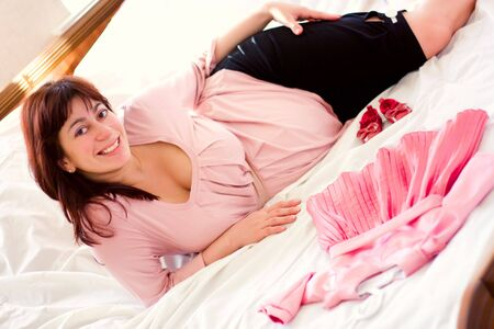 young beautiful pregnant woman with small pink dress Stock Photo