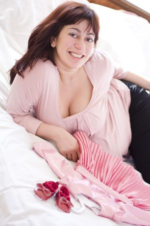 young beautiful pregnant woman with small pink dress photo