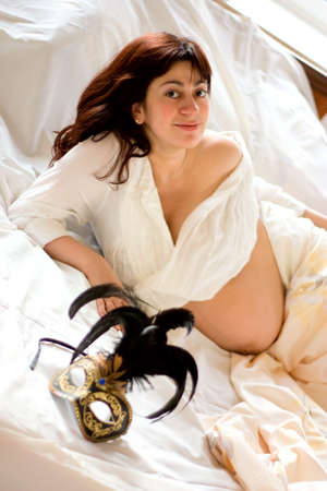 pregnant sexy: young beautiful pregnant woman lying on bed Stock Photo