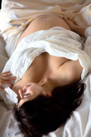 nacimiento: hermosa joven mujer embarazada tumbada en la cama Foto de archivo