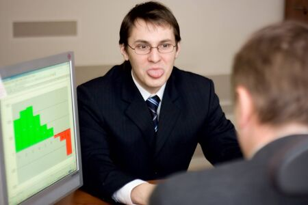 young employee puting out his tongue at his boss