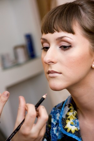 beautician creating wedding makeup for a young woman