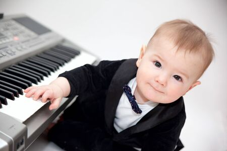 interested baby: little boy in tailcoat playing piano Stock Photo