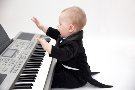 little boy in tailcoat playing piano photo
