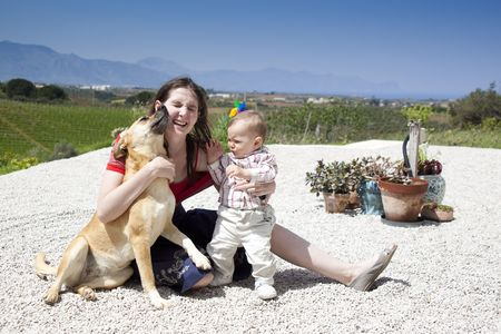 mother and baby son playing with dog outdoors