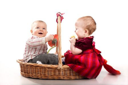 baby boy and baby girl playing together in basket