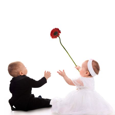 petit garçon et la fille qui joue avec fleur rouge