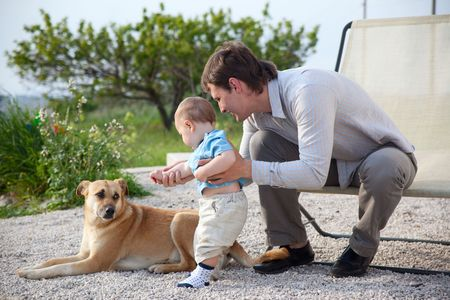 father helping his baby son to communicate with dog