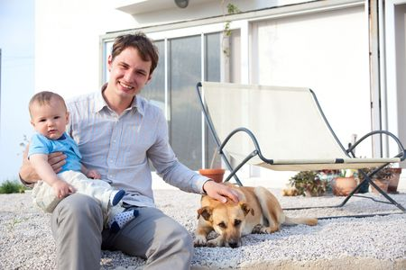 father with his baby son and dog in front of a house Stock Photo - 4844380