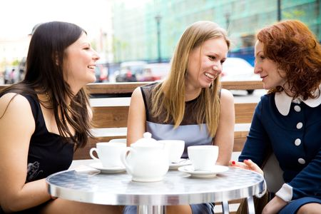 lunch meeting: three beautiful women drinking coffee outdoors