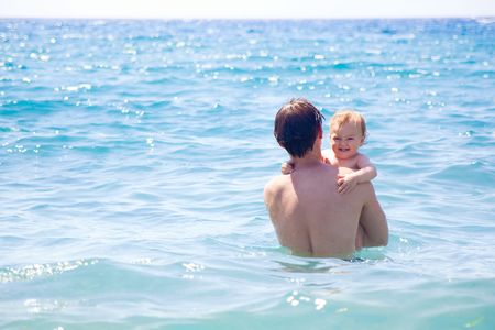 dad and son bathing together in the sea photo
