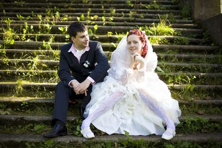 bride and bridegroom sitting on the old stairs of an ancient palace