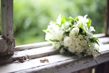 bouquet of white flowers and 2 wedding rings lying on an old windowsill