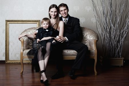 portrait of happy family sitting on the couch photo