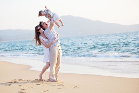 happy young family having fun on the beach photo