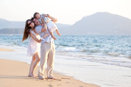 happy young family having fun on the beach Stock Photo