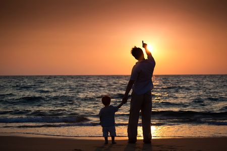 dad and his little son standing on the beach and looking at sunset