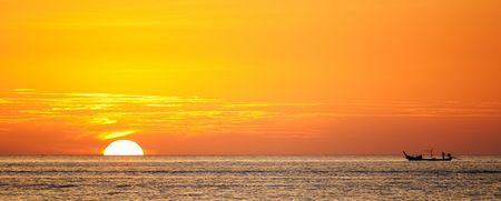 sillhouette: sillhouette of a boat against the orange sunset