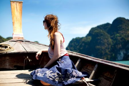 prow: young woman sitting on a prow of a boat  Stock Photo