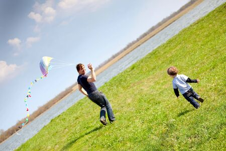 happy dad and son flying a kite together Stock Photo