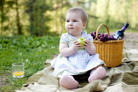 cute baby girl having lunch in the nature