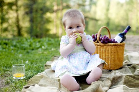 baby girl eating green apple in the nature
