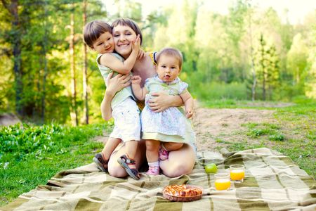 happy mother hugging her 2 children: son and daughter Standard-Bild