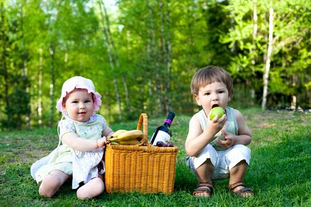 baby girl and little boy having picnic in the nature