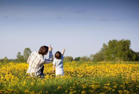 dad and little son pointing up in the field of dandelions