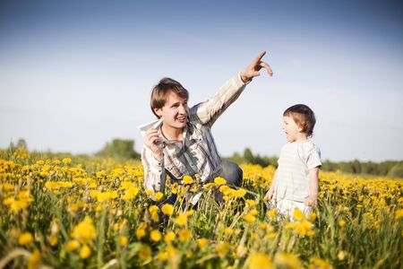 happy dad and son launch paper plane in the field of dandelions photo