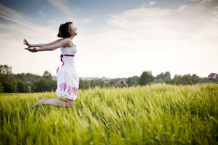 young happy woman jumping in the field Standard-Bild