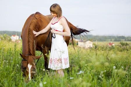 femme a cheval: jeune femme avec cheval dans le domaine