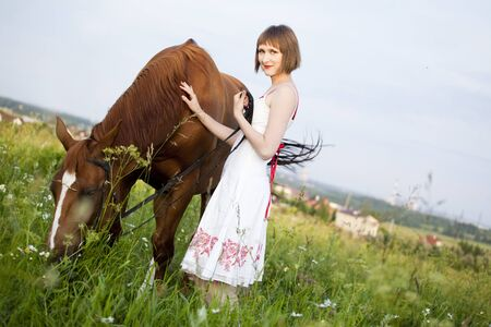 young woman with horse in the field Stock Photo - 7755559