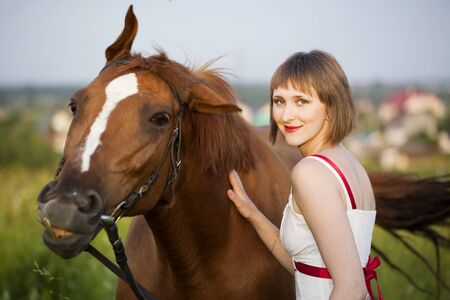 young woman with horse in the field photo