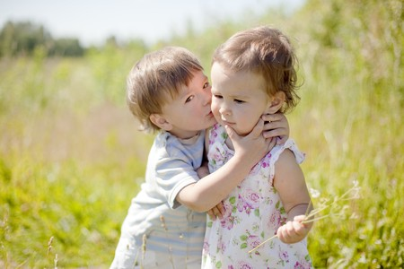 little boy kissing little girl outdoors