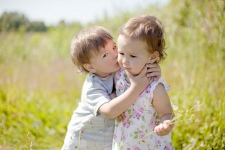 s embrasser: petit gar�on embrasser ext�rieur petite fille Banque d'images