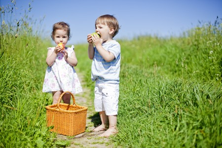 little children eating fruits outdoors in the summer