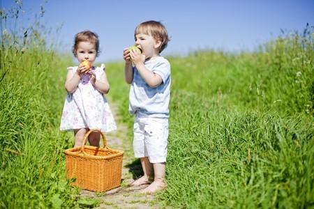 niños pequeños que comer frutas al aire libre en el verano