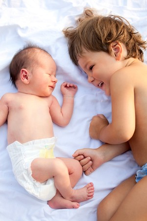 two baby brothers lying together and smiling
