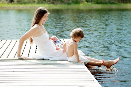 young beautiful mother spending time with her children outdoors photo