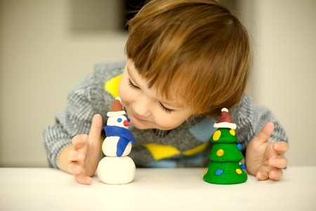 a child making a snowman and christmas tree of plasticine photo
