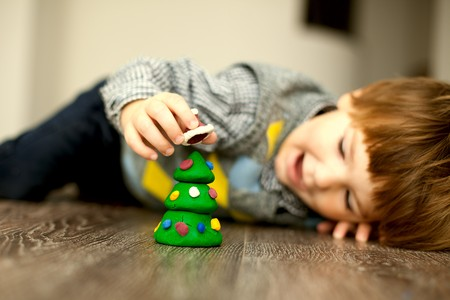 a child making a snowman and christmas tree of plasticine Standard-Bild