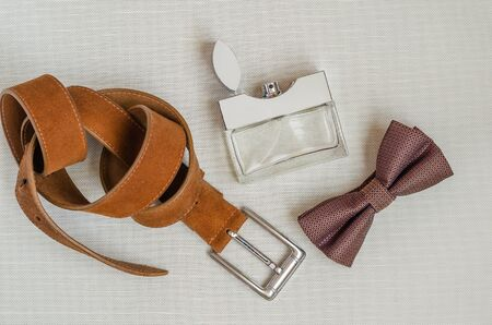 Bow tie, perfume and leather trouser belt. A gift to her husband, lover, father, boyfriend. View from above. Selective focus.